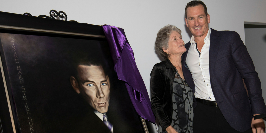 Travis and his mother Denise unveil a portrait of his grandfather, Jack O'Brien